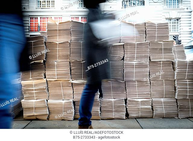 Unrecognizable people passing by newspaper bundles stacked on the street. London, England