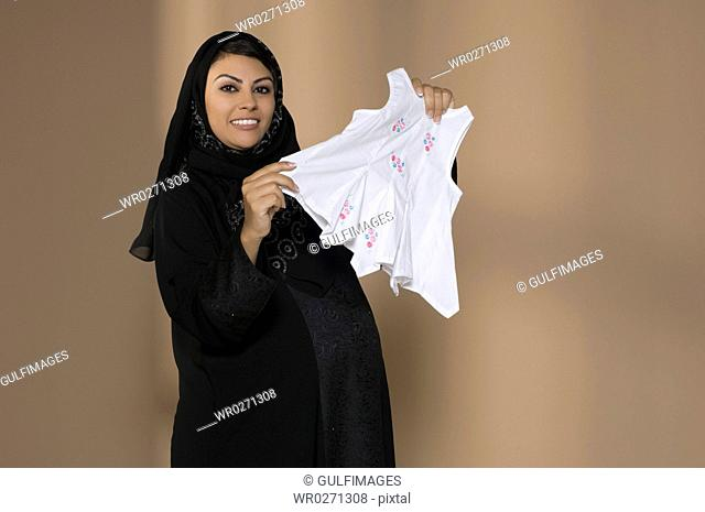 Pregnant woman holding baby cloth,smiling,portrait