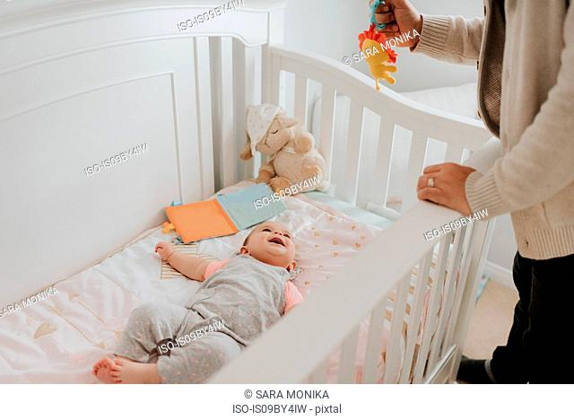 Father putting baby daughter to bed in crib