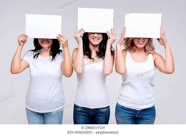 Universal language. Neat diverse women of different backgrounds posing with white sheets of paper and covering their eyes accentuating their beautiful smiles
