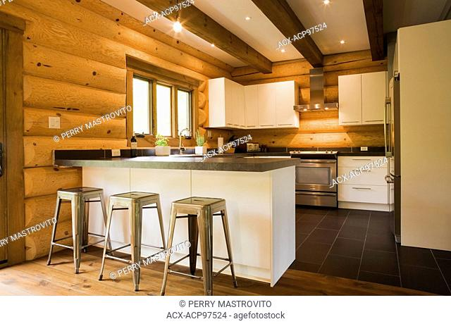 Kitchen with white wooden cabinets, metal barstools and wooden stairs with black wrought iron railings inside a cottage style log home, Quebec, Canada