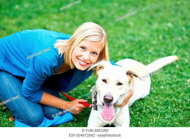 Happy young woman outdoors with her cute labrador