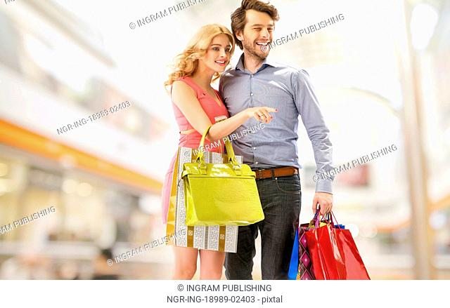 Young cheerful couple with a bunch of shopping bags