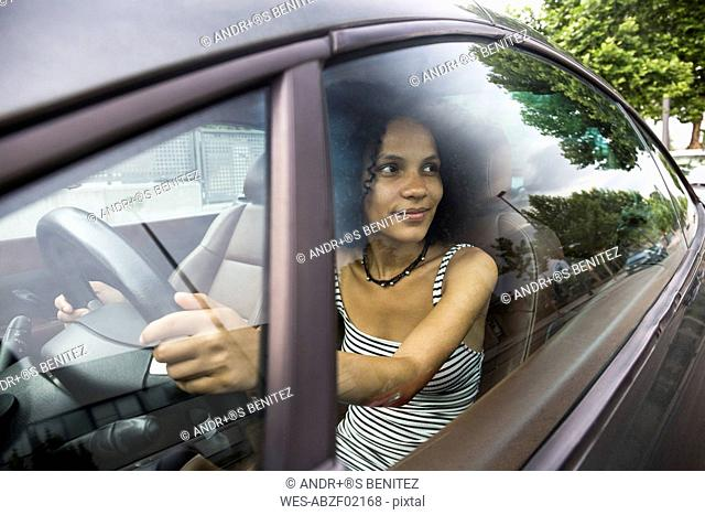 Woman driving a car looking out a car window