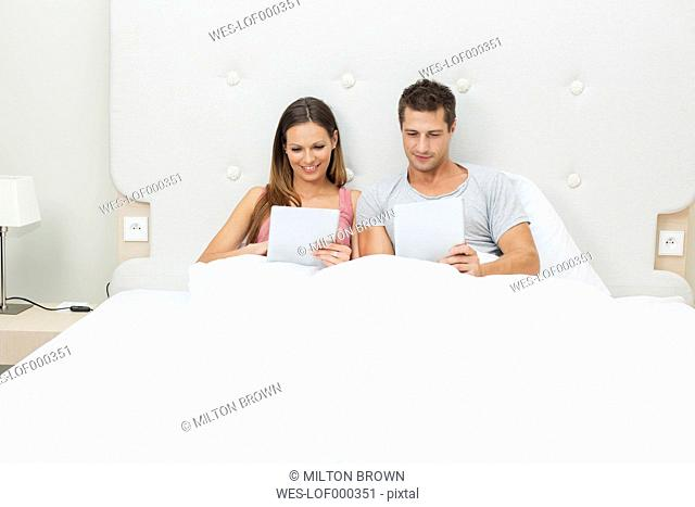 Young couple sitting side by side in hotel bed looking at smartphone and tablet computer
