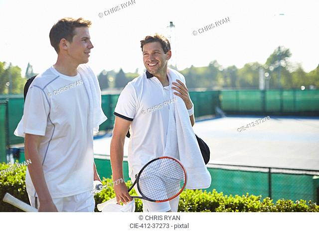 Smiling young male tennis players walking with tennis rackets along sunny tennis court