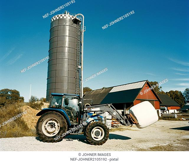 tractor in front of a silo