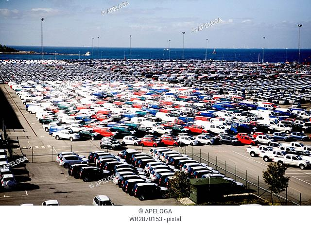 Aerial view of car parking lot by sea against sky