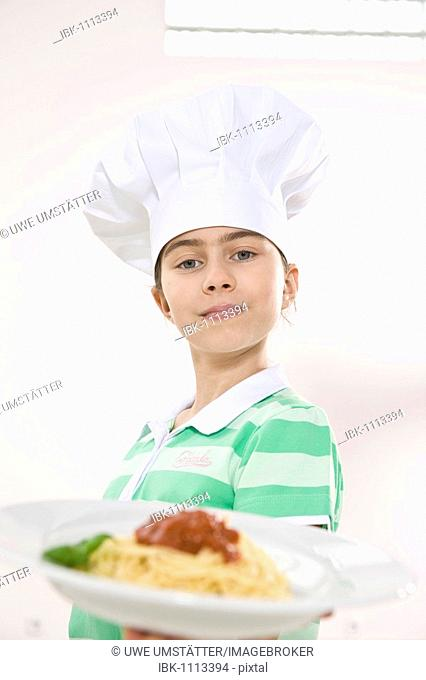 Girl wearing a chef's hat holding a plate of spaghetti