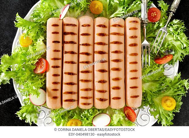 Plate with grilled Vienna sausage on fresh lettuce, tomatoes and radish salad, above shot
