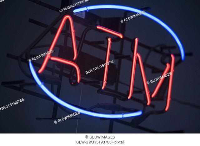 Low angle view of an ATM sign lit at night