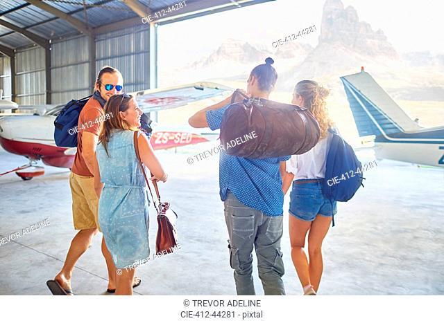 Friends with bags walking in airplane hangar