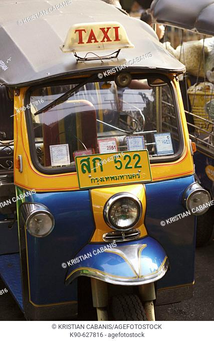 A Tuk Tuk - the famous three wheel taxi of Bangkok, notorious for its noise and pollution, waiting for customer at the roaside, Bangkok, Thailand