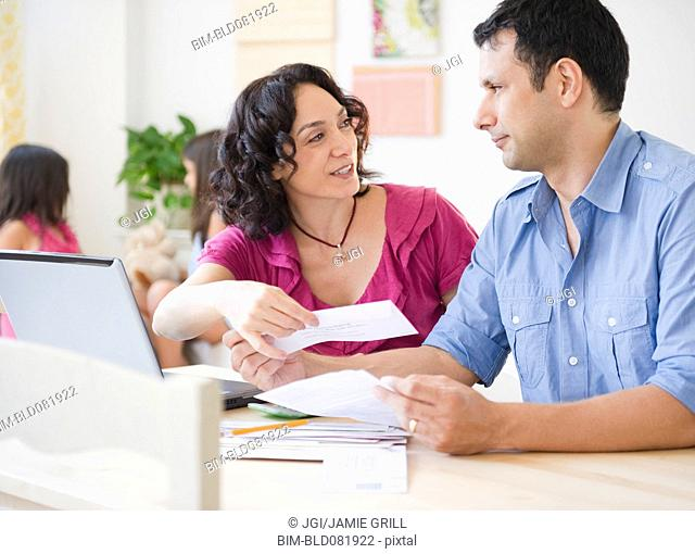 Husband and wife paying bills online with laptop