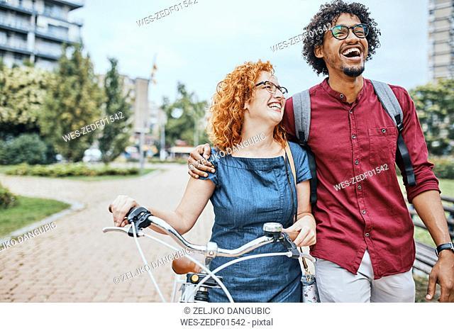 Friends walking in park, talking, woman pushing bicycle