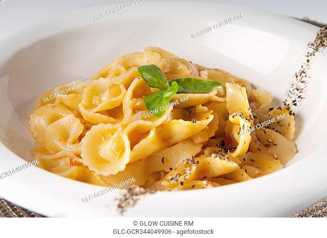 Close-up of fresh pepper and basil garnished pasta