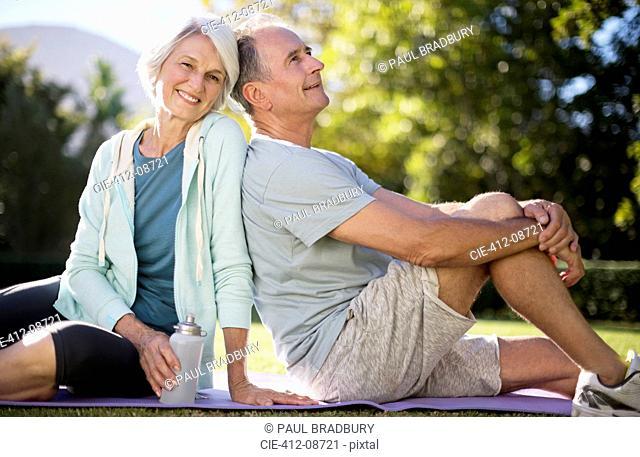 Senior couple sitting on yoga mat in park