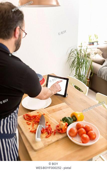 Man using digital tablet while preparing food in the kitchen