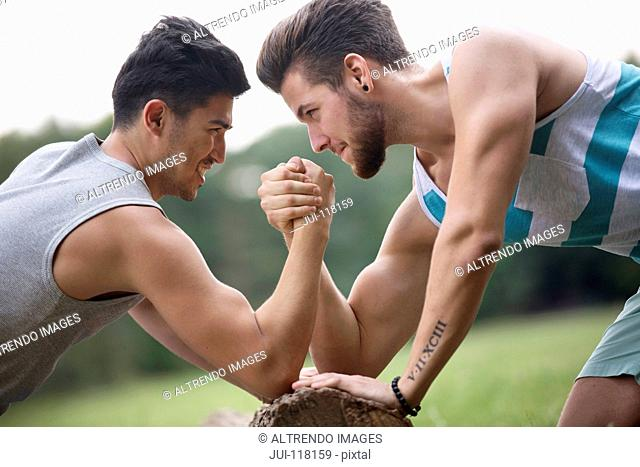 Two Male Friends Arm Wrestling Outdoors Together
