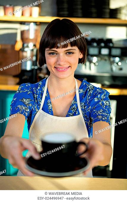 Portrait of waitress offering a cup of coffee