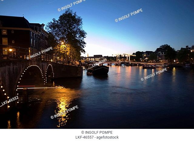 Boats, Magere Brug, Amstel, View over illuminated Magere Brug Skinny Bridge, to Stopera and Zuiderkerk at night, Amsterdam, Holland, Netherlands
