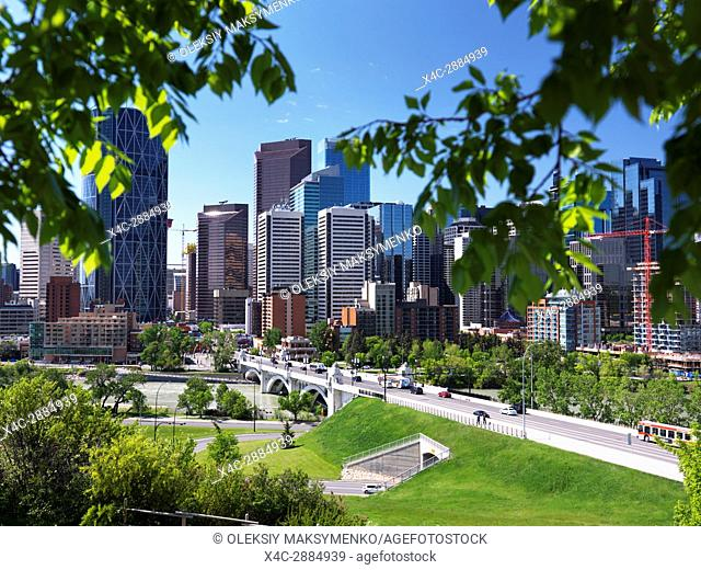 Calgary city downtown skyline with Centre Street Bridge over Bow river artistic scenery framed by green tree leaves. Calgary, Alberta, Canada 2017