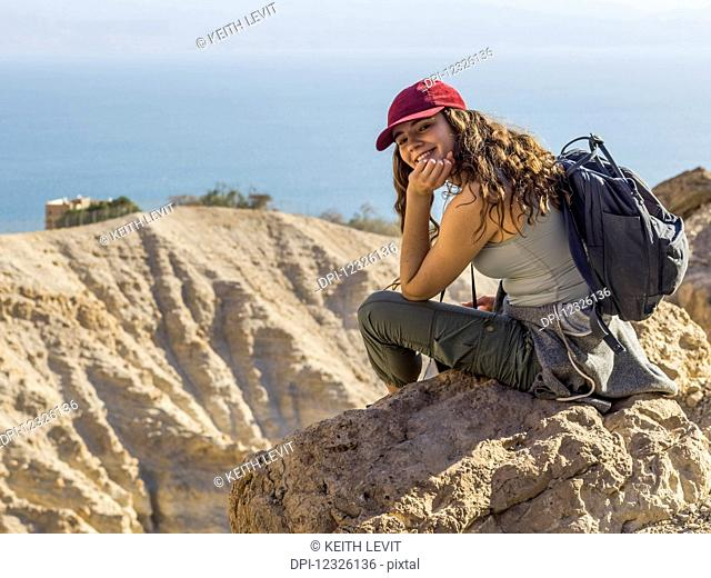A young woman sits on a rock looking back and posing for the camera with a view of Ein Gedi Nature Reserve, Dead Sea District; South Region, Israel