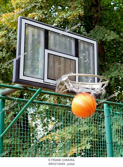 Basketball Board with Basket and Orange Ball Outdoors