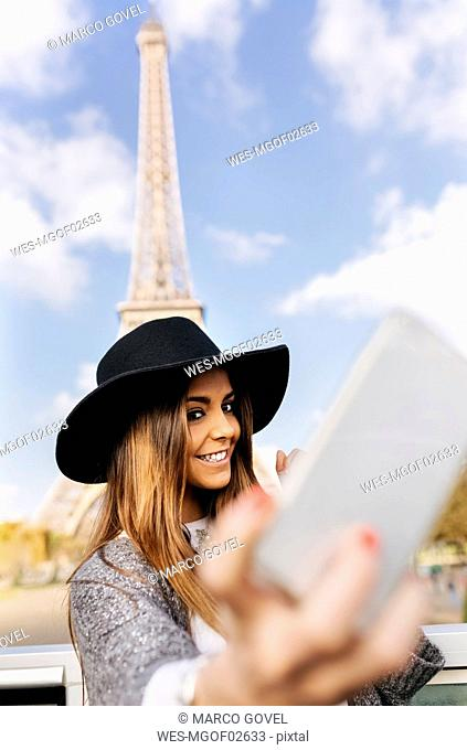 France, Paris, smiling woman taking a selfie in front of Eiffel Tower