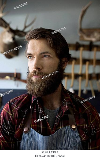 Close up pensive bearded shop worker