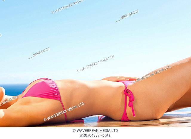 Young woman enjoying sunny day lying on the pool edge