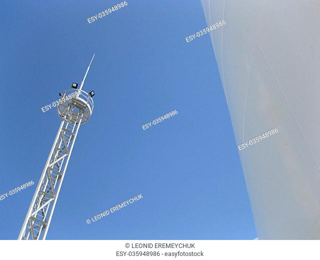 White tank and tower lighting on the sky background. Equipment for primary oil refining