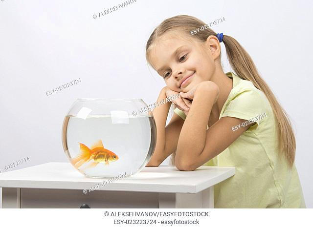 Happy six year old girl sits at a table at the fishbowl with goldfish