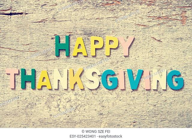 """The colorful words """"""""HAPPY THANKSGIVING"""""""" made with wooden letters on old wooden plank"""