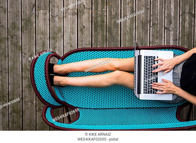 Young woman sitting on turquoise couch on terrace using laptop, top view