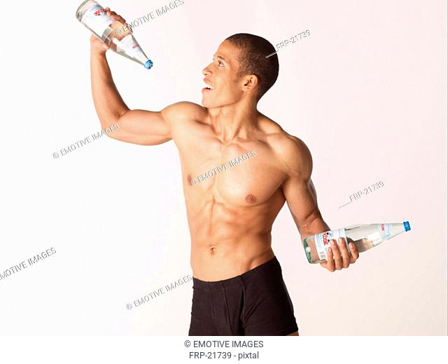 Content barechested man holding water bottles