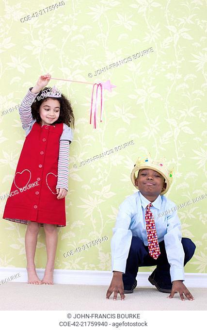 Girl Waving Magic Wand at Boy Acting Like Frog
