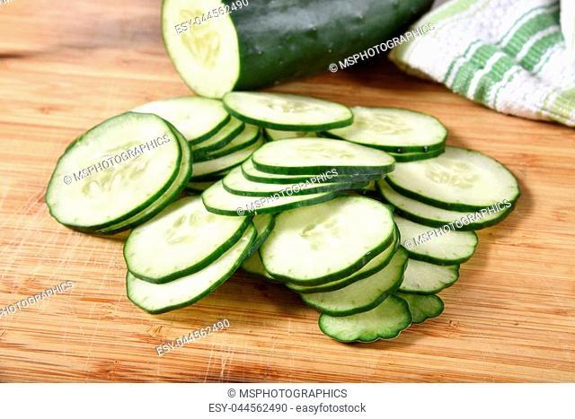 A mound ot thin sliced cucumber on a cutting board