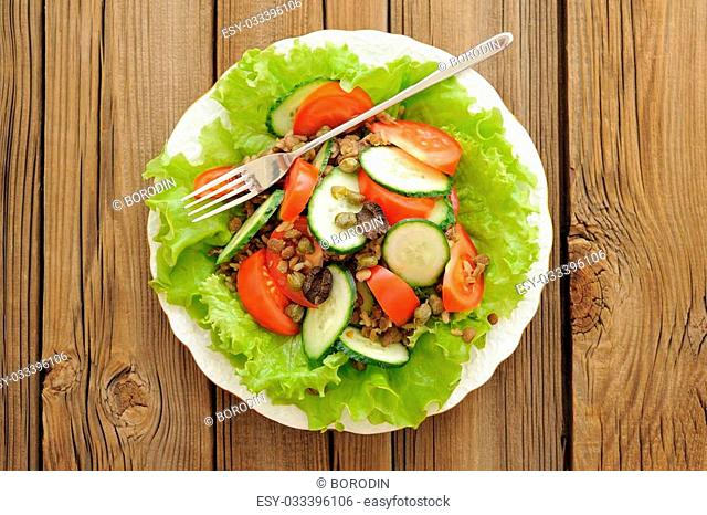 Lentil salad with tomatoes, cucumbers, capers and lettuce with thin fork on wooden table top view horizontal