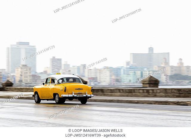 Yellow car on the wet Malecon highway in Havana