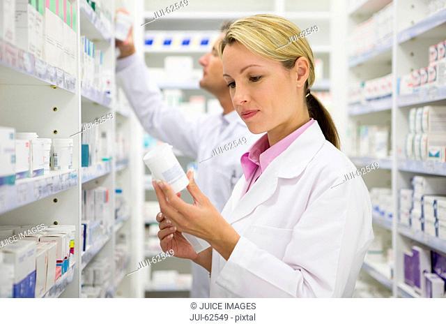 Pharmacist reading bottle of prescription medication in pharmacy