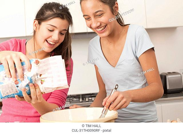 teenage girls preparing food in kitchen