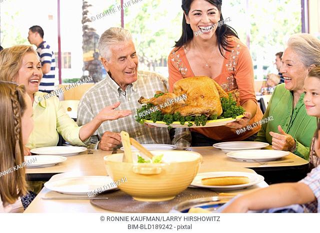 Hispanic family eating Thanksgiving dinner together