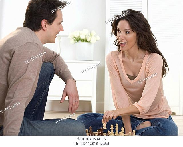 Couple talking and playing chess