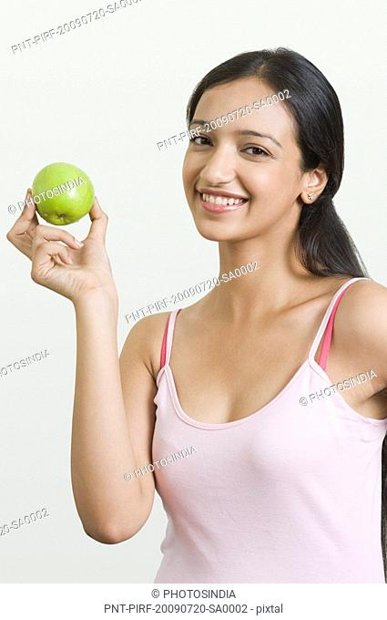 Woman showing a green apple and smiling