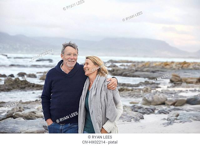 Smiling senior couple walking on winter beach