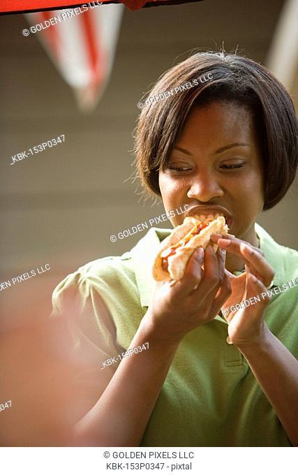 A young woman eating hotdog