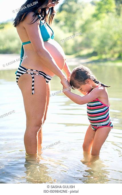 Pregnant mother and daughter standing in lake, holding hands