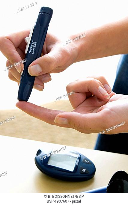 TEST FOR DIABETES Model. Woman using a lancing device to do a test of glycemia (diabetes). We can see the glucometer that will mesure the rate of glucose in the...