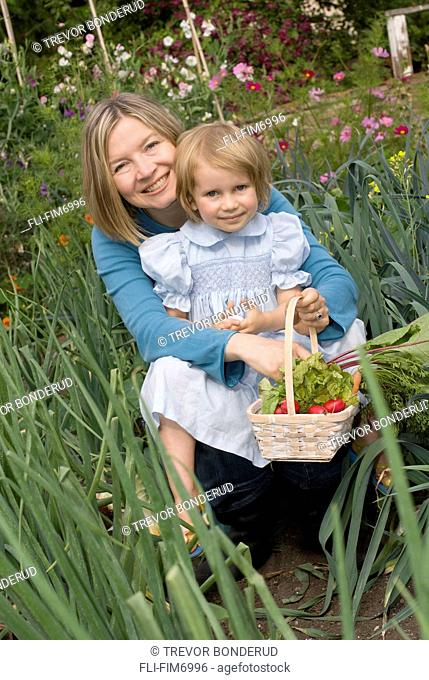 Mother and daughter in an organic garden, Victoria, British Columbia